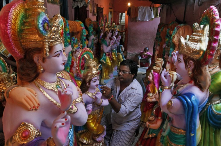 An Indian artisan gives finishing touches to an idol of Lord Krishna ahead of Janmashtami celebrations in Ahmadabad, India, Tuesday, Sept. 1, 2015. Janmashtami is the birthday of Hindu God Krishna and will be celebrated on Sept. 5. (AP Photo/Ajit Solanki)