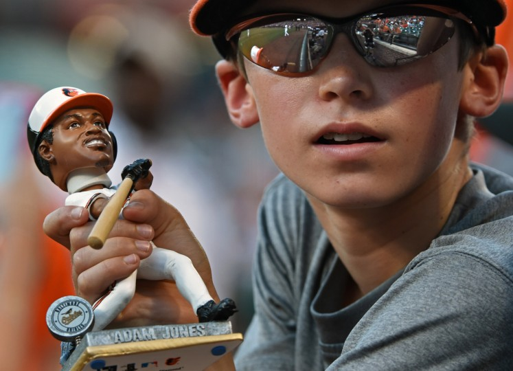A young fan hopes Orioles center-fielder Adam Jones will  come by and sign his bobble-head doll. (Kenneth K. Lam/Baltimore Sun)