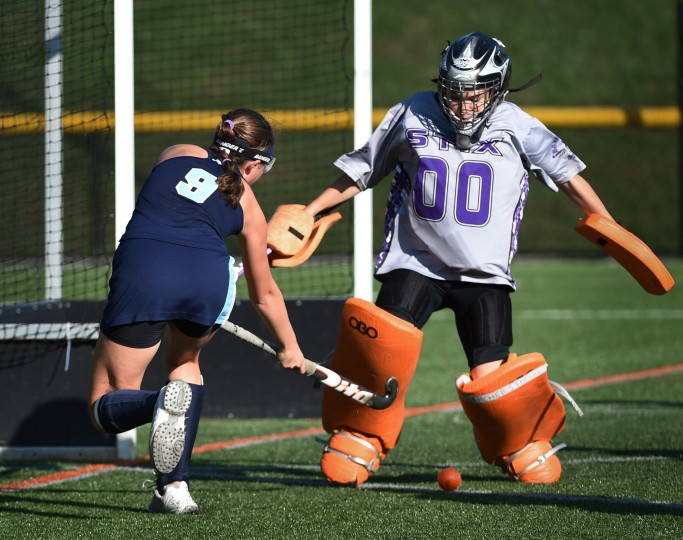 Garrison Forest's Hailey Mules, left, shoots the ball between the legs of McDonoghj goalie Nadia Hyatt in the first half. Garrison Forest defeated McDonogh by score of 3 to 2 in field hockey. (Kenneth K. Lam/Baltimore Sun)