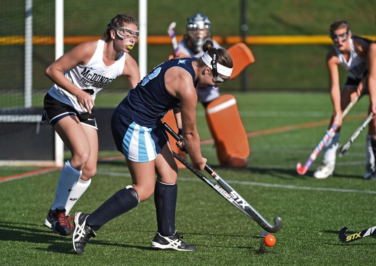 Owings Mills, MD--10/7/15-- Garrison Forest's Natakie Adamez, center, takes a shot against McDonogh's Emma Schettig, left, in the first half. Garrison Forest defeated McDonogh by score of 3 to 2 in field hockey. (Kenneth K. Lam/Baltimore Sun)