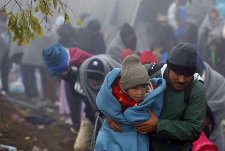 A migrant carries a child on the field near the village of Berkasovo, Serbia, Thursday, Oct. 22, 2015. Many migrants from the Middle East, Asia and Africa expressed bewilderment and disappointment because they had been told as they began their journeys in Turkey that the hard part would end once they reached EU countries like Croatia and Slovenia. (AP Photo/Darko Vojinovic)