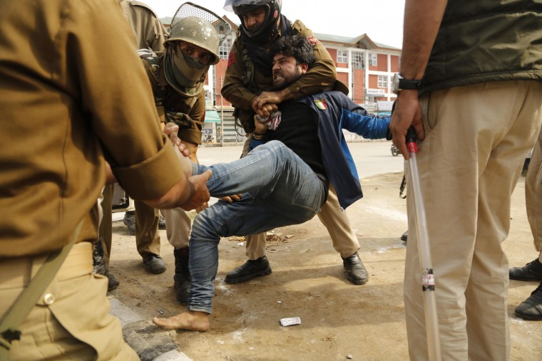Indian policemen detain a Kashmiri Shiite Muslim who participated in a religious procession during restrictions imposed in Srinagar, Indian controlled Kashmir, Thursday, Oct. 22, 2015. Police imposed restrictions in some parts of Srinagar fearing religious processions marking the Muslim month of Muharram would turn into anti-India protests. (AP Photo/Mukhtar Khan)