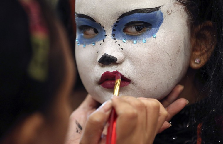 Filipino girl Mikaela Rayll Mangahas has her make-up done as she attends a Halloween event in Manila, Philippines on Sunday, Oct. 25, 2015. (AP Photo/Aaron Favila)