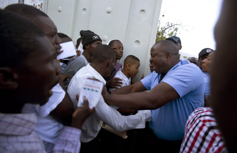 A security guard pushes voters back in order to keep a polling station from reaching over capacity during elections in Port-au-Prince, Haiti, Sunday Oct. 25, 2015. The country is holding the first-round presidential vote Sunday along with balloting for numerous legislative races and local offices. (AP Photo/Dieu Nalio Chery)