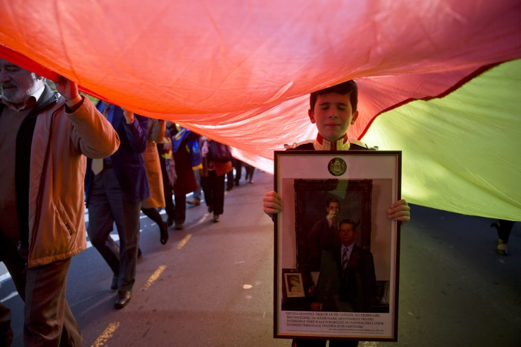 A Romanian boy, wearing a royal uniform holds a picture of former Romanian King Michael I as supporters of the monarchy march to celebrate the king's 94th birthday, in Bucharest, Romania, Sunday, Oct. 25, 2015. Monarchy supporters carried a 150 meters long flag on a main boulevard in the Romanian capital to celebrate the former king's birthday. (AP Photo/Vadim Ghirda)