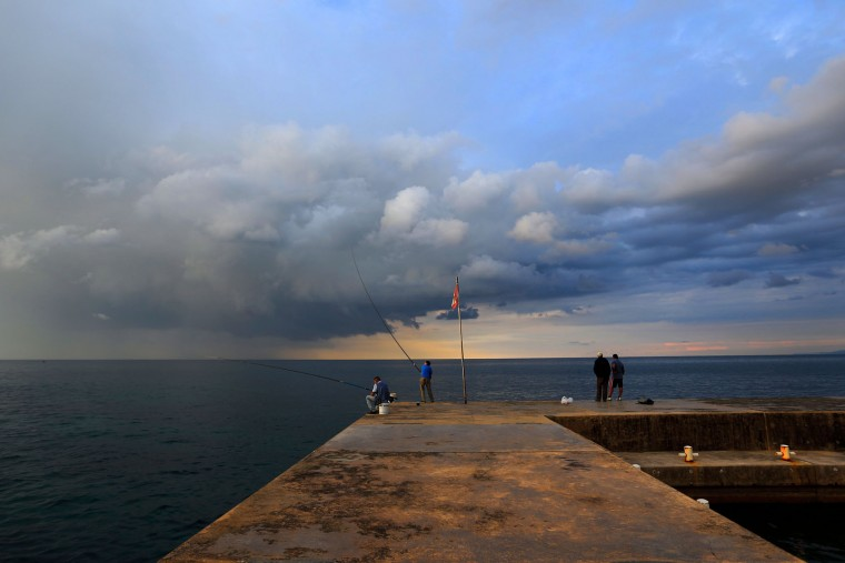 Lebanese fishermen stand on a breakwater along the Beirut coastline as they fish while the sun sets over the Mediterranean Sea in Beirut, Lebanon, Thursday, Oct. 29, 2015. (AP Photo/Hassan Ammar)