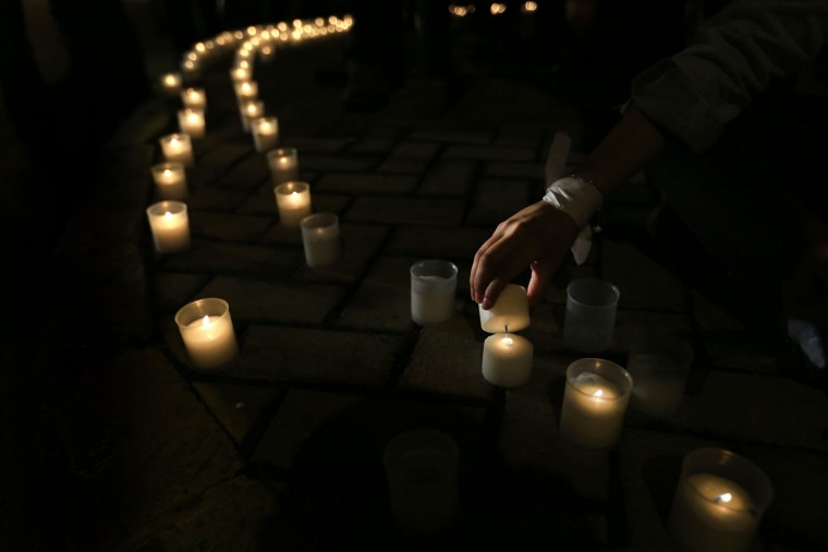 A Lebanese activist lights candles on the ground during a protest against the ongoing trash crisis and government corruption, in Beirut, Lebanon, Thursday, Oct. 29, 2015. A crisis over uncollected trash in the Lebanese capital has ignited the largest protests in the country in years and has emerged as a festering symbol of the government's paralysis and failure to provide basic services. (AP Photo/Hassan Ammar)