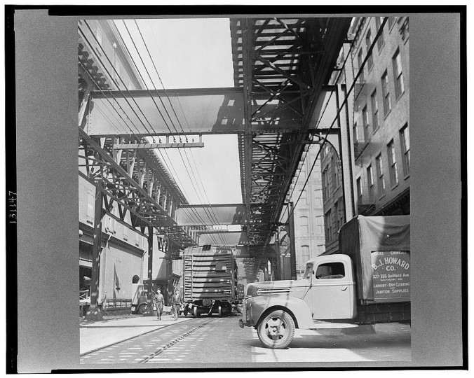"""Trucks and trains unloading goods underneath an elevated trolley"""