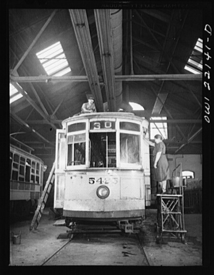 """Painting the roof and washing the windows of a 1912 trolley at the paint shop of the maintenance terminal of the Baltimore Transit Company"""