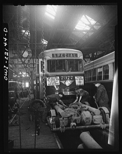 """Repairing the motor of a PCC trolley. Most recent trolley model designed in 1936 by a group of manufacturers and transit companies in an effort to standardize, simplify, and bring down the price; at the damage shop, maintenance terminal of the Baltimore Transit Company"""