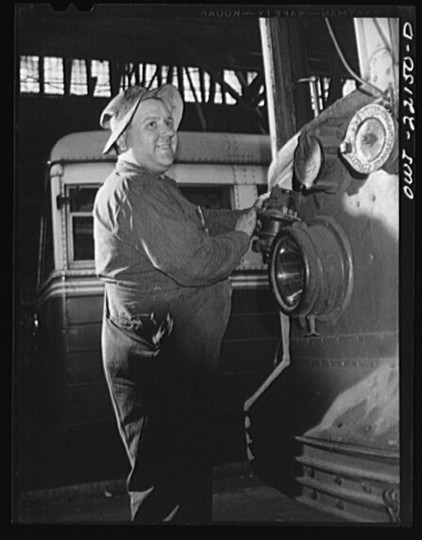 """Repairing electric connector at the end of a 1919 trolley, at the damage repair shop of the maintenance terminal of the Baltimore Transit Company"""