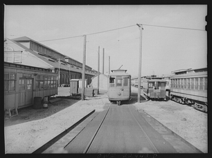 """The yard of the Washington terminal, maintenance plant of the Baltimore Transit Company. From left to right: old trolley made into a smoker for employees; a work car; and old horse car. The Baltimore Trust building on the horizon"""