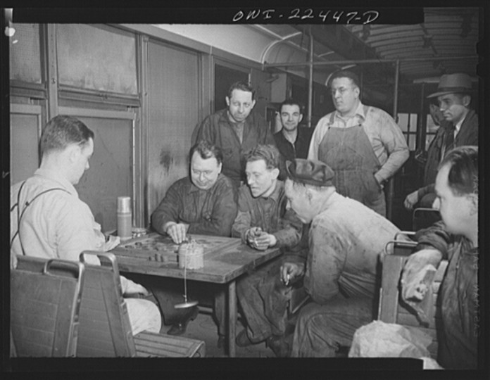 """Employees at the maintenance terminal of the Baltimore Transit Company having lunch and playing checkers in an old trolley made into a smoker"""