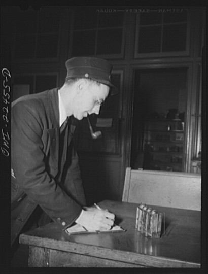 """Trolley conductor counting his receipts at the Park Terminal, dispatching center of the Baltimore Transit Company"""
