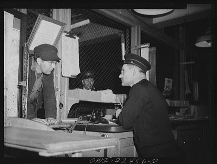 """Trolley dispatcher in his cage at the Park Terminal listening to a report of the engineer on the condition of a car. Each car receives a routine checkup daily"""