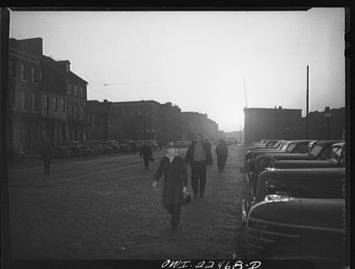 """""""Employees of the Bethlehem Fairfield shipyard hurrying to catch the six a.m. ferry across Curtis Bay to work. The street is lined with their parked cars."""" Marjory Collins, April 1943"""