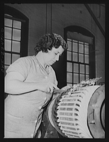 """Woman winding the armature of a trolley motor in the armature shop of Washington terminal, maintenance plant of the Baltimore Transit Company. This woman was first employed by the company during the last war. No new women have been hired in the maintenance plant in this emergency"""