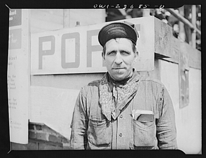 Bethlehem-Fairfield shipyards, Baltimore, Maryland. Worker in front of a port sign on the shipways. (Arthur S. Siegel / May 1943)