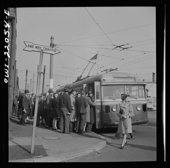 """""""Workers boarding a trackless trolley at four p.m. Trackless trolleys are more economical than buses to run because they require no gas; but do use tires. They are run by electric power in wires above the street and can be manipulated from one side of the street to the other."""" Marjory Collins, April 1943"""