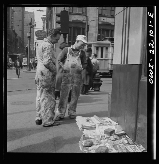 """""""Workers reading the newsstand papers while waiting for a trolley after work."""" Marjory Collins, April 1943"""