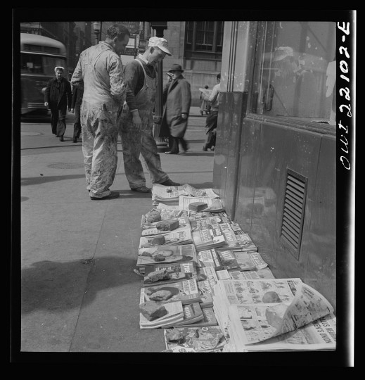 """Workers reading the newsstand papers while waiting for a trolley after work"""