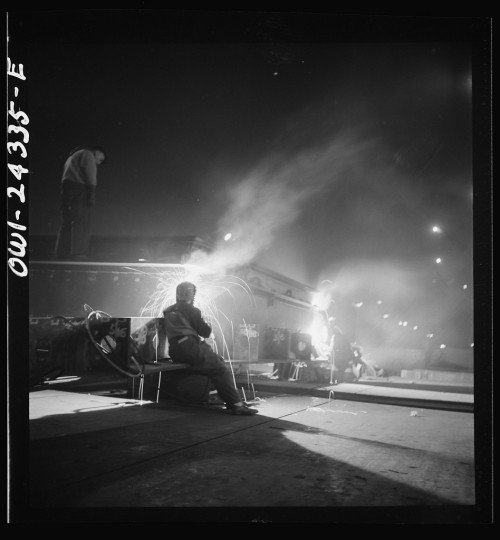 """""""Third shift workers waiting on street corner to be picked up by shared cars around midnight."""" Marjory Collins, April, 1943"""