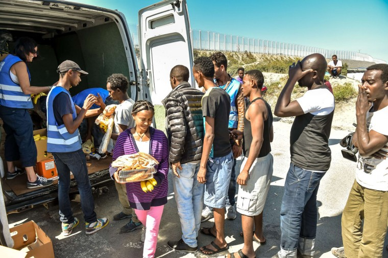 """This file photo taken on August 8, 2015 shows migrants waiting to receive food from the humanitarian organization """"L'Auberge des Migrants"""" at the entrance of the migrant camp dubbed 'New Jungle' in Calais, northern France. (PHILIPPE HUGUEN/AFP/Getty Images)"""