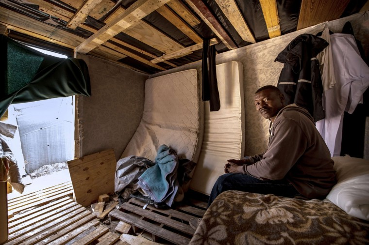 "Abdel Hafez Seddig, a 33-year-old migrant from Sudan, takes cover from the rain inside a hut at a makeshift camp known as the ""New Jungle"" in Calais in northern France on September 14, 2015. Under an agreement between the British and French governments, British border controls are carried out on the French side of the Channel Tunnel, making Calais the focal point of attempts by migrants to cross into England. Thousands of migrants over the summer attempted to cross the Channel Tunnel between Britain and France, which later stepped up border controls. (PHILIPPE HUGUEN/AFP/Getty Images)"