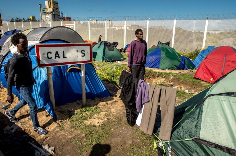 "Migrants camp at a site dubbed the ""New Jungle,"" where some 3,000 people have set up camp -- most seeking desperately to get to England, in Calais. The slum-like migrant camp sprung up after the closure of notorious Red Cross camp Sangatte in 2002, which had become overcrowded and prone to violent riots. However migrants and refugees have kept coming and the ""New Jungle"" has swelled along with the numbers of those making often deadly attempts to smuggle themselves across the Channel. (PHILIPPE HUGUEN/AFP/Getty Images)"