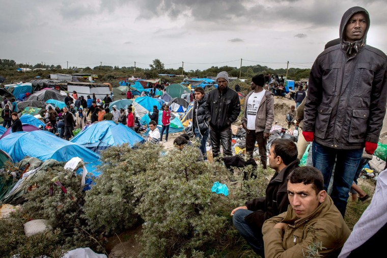 "People stand at a site dubbed the ""New Jungle,"" where some 3,000 people have set up camp -- most seeking desperately to get to England. (PHILIPPE HUGUEN/AFP/Getty Images)"