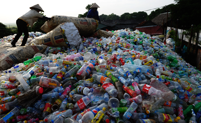 This picture taken on October Sunday shows workers standing on a large pile of used plastic bottles at the roadside shop of a trader of recyclable items in Thach That district on the outskirts of Hanoi. The traders buy the recyclable items from hundreds of mobile collectors before selling them on to factories for recycling. (HOANG DINH NAM/AFP/Getty Images)