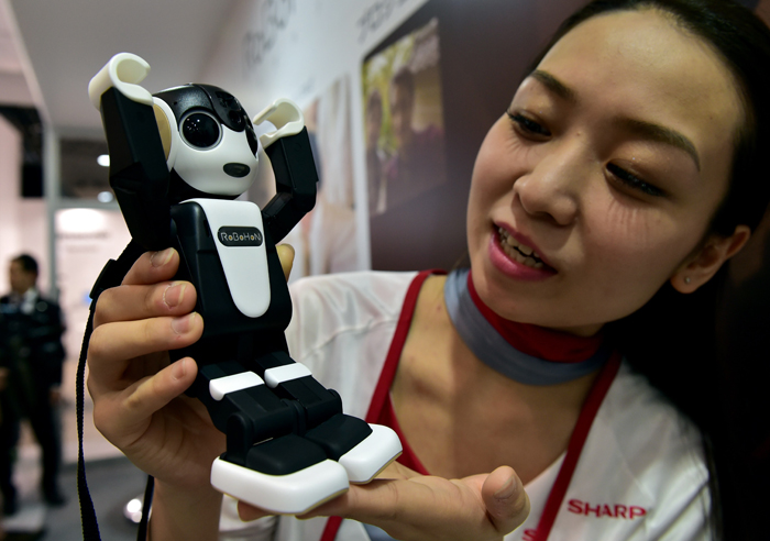 "Japan's electronics giant Sharp unveils the humanoid robot shaped smartphone ""Robohon"" at a preview of Asia's largest electronics trade show Ceatec in Chiba on October 6, 2015. The Robohon, designed by Japan's famous robot creator Tomotaka Takahashi, can walk, speak, dance and make phone calls. It is to go on sale early next year.  (YOSHIKAZU TSUNO/AFP/Getty Images)"