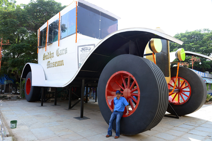 Indian car designer Sudhakar Yadav poses next to a large stationary car modeled on the 1922 Ford Tourer at the Sudha Cars Museum in Hyderabad on Tuesday. The car, which stands 26 feet tall and 50 feet long, was built in an attempt at the Guinness World Record for largest stationary car. (NOAH SEELAM/AFP/Getty Images)