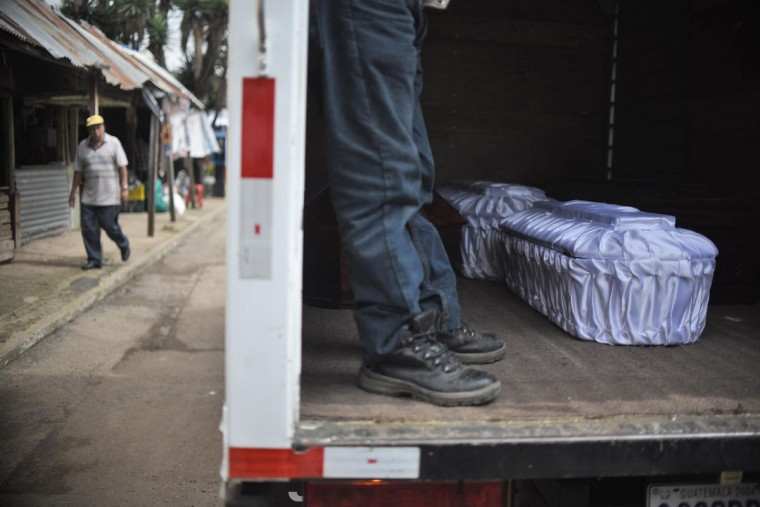 Two coffins of victims of past Thursday's landslide are seen on a truck during a funeral in Santa Catarina Pinula municipality, some 15 km east of Guatemala City, on October 6, 2015. At least 161 people were killed when massive mudslides buried scores of homes on the outskirts of Guatemala's capital city, as the death toll continues to climb. An estimated 300 people are still missing. (AFP Photo/Johan Ordonez)