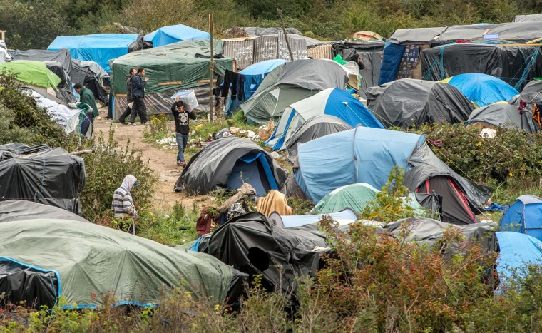 "People stand next to a site dubbed the ""New Jungle,"" where some 3,000 people have set up camp -- most seeking desperately to get to England, in Calais on October 7, 2015. (PHILIPPE HUGUEN/AFP/Getty Images)"