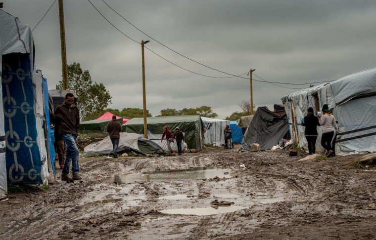 """People stand on a site dubbed the """"New Jungle,"""" where some 3,000 people have set up camp -- most seeking desperately to get to England, in Calais on October 7, 2015. (PHILIPPE HUGUEN/AFP/Getty Images)"""