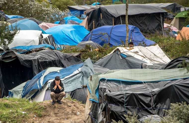 """A picture taken in Calais on October 7, 2015 shows a site dubbed the """"New Jungle"""", where some 3,000 people have set up camp -- most seeking desperately to get to England, . The slum-like migrant camp sprung up after the closure of notorious Red Cross camp Sangatte in 2002, which had become overcrowded and prone to violent riots. However migrants and refugees have kept coming and the """"New Jungle"""" has swelled along with the numbers of those making often deadly attempts to smuggle themselves across the Channel. (AFP Photo/Philippe Huguen)"""