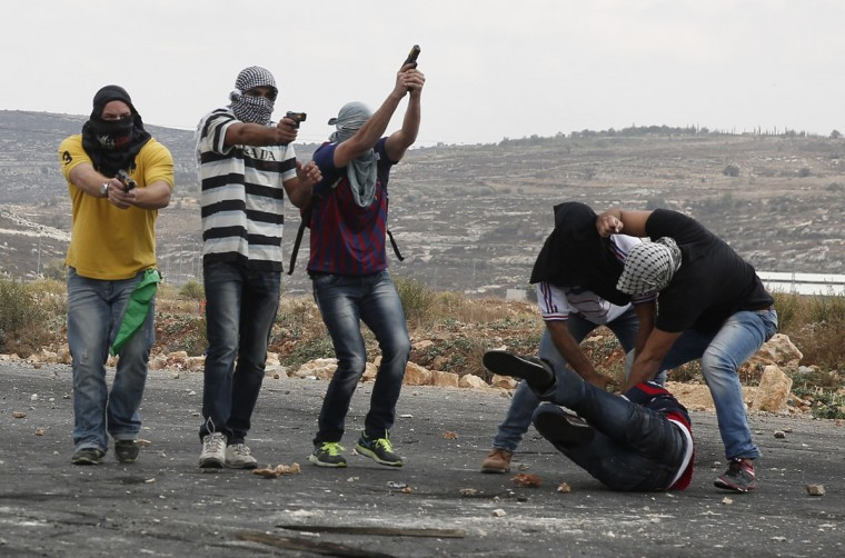 Infiltrated members of the Israeli security forces detain a Palestinian stone thrower and aim their weapons at fellow protesters during clashes in Beit El, on the outskirts of the West Bank city of Ramallah, on October 7, 2015. New violence rocked Israel and the Israeli-occupied West Bank, including a stabbing in annexed east Jerusalem, even as Israel and Palestinian president Mahmud Abbas took steps to ease tensions. (AFP Photo/Abbas Momani)