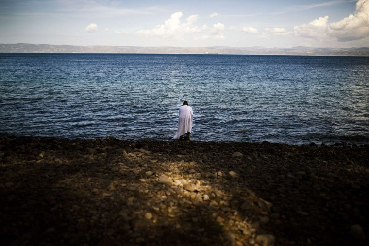 A woman stands on the beach, shortly after she arrived on the Greek island of Lesbos after crossing the Aegean sea from Turkey on October 12, 2015. Greece was hit by a huge new surge in migrants as the United Nations on October 9 approved a European seize-and-destroy military operation against people smugglers in the Mediterranean. (AFP Photo/Dimitar Dilkoff)