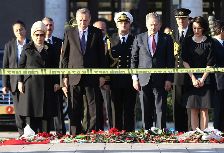 Turkey's President Recep Tayyip Erdogan (2nd L), Finland's President Sauli Niinisto (2nd R), and their wives Emine Erdogan (L) and Jenni Haukio attend a wreath-laying ceremony at the site of the weekend twin bombings in Ankara in front of the city's railway station on October 14, 2015. Turkish President Recep Tayyip Erdogan paid homage on Wednesday at the site of the twin bombings in Ankara, where two suicide bombers blew themselves up on October 10 in a crowd of leftist and pro-Kurdish activists attending a peace rally, killing 97 people. The government has said the Islamic State (IS) group is the prime suspect behind the attack, which also injured more than 500. (AFP Photo/Adem Altan)