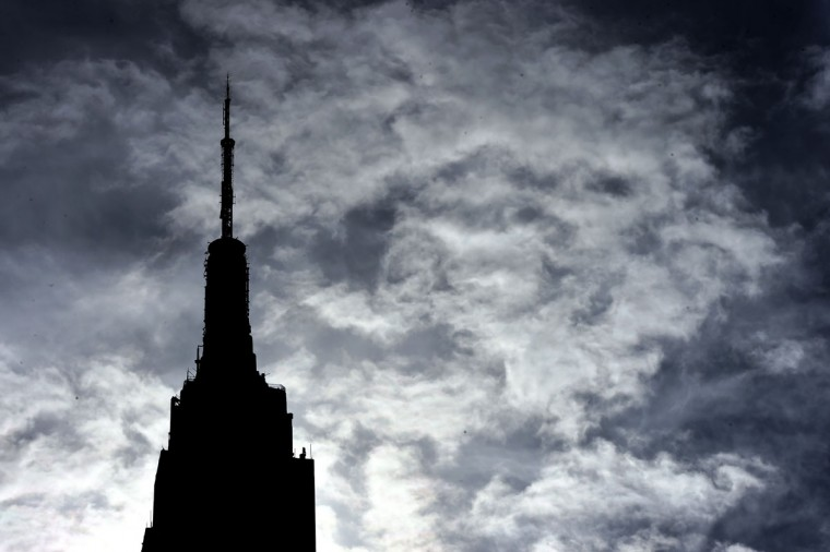 The Empire State Building is silhouetted against the clouds in the sky in Midtown Manhattan October14, 2015. The city has been experiencing warmer than normal weather with temperatures in the 70s. (AFP Photo/Timothy Clary)