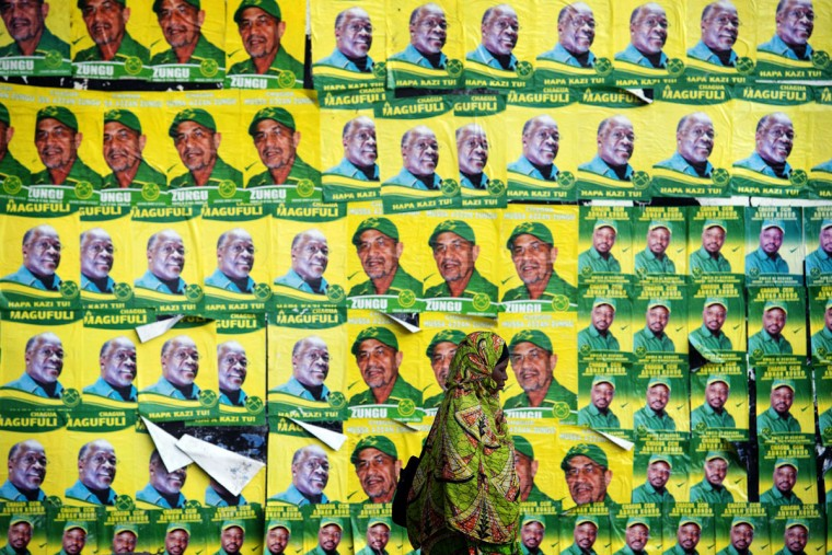 A woman walks past posters for ruling party Chama Cha Mapinduzi (CCM) presidential candidate John Magufuli and parliamentary candidate Hassan Zungu on October 20, 2015 in Dar es Salaam. (AFP Photo/Daniel Hayduk)