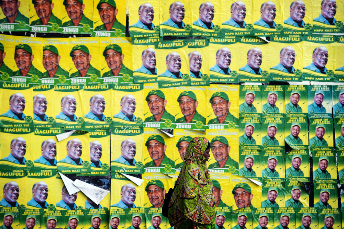 A woman walks past posters for ruling party chama cha mapinduzi ccm presidential candidate john magufuli and parliamentary candidate hassan zungu on