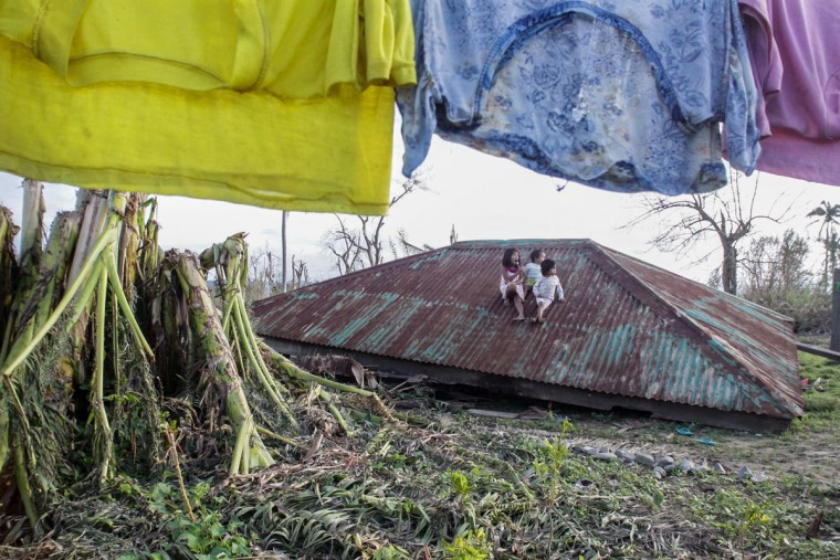 Children sit on the roof of a house blown over by typhoon Koppu in Casiguran town, Auroran province northeast of Manila on October 21, 2015, days after the typhoon devastated the province. Widespread flooding in the Philippines caused by a powerful typhoon eased on October 21 but the storm's death toll climbed to 47 and tens of thousands of people remained in evacuation centres. (AFP Photo/Dante Diosina jr)