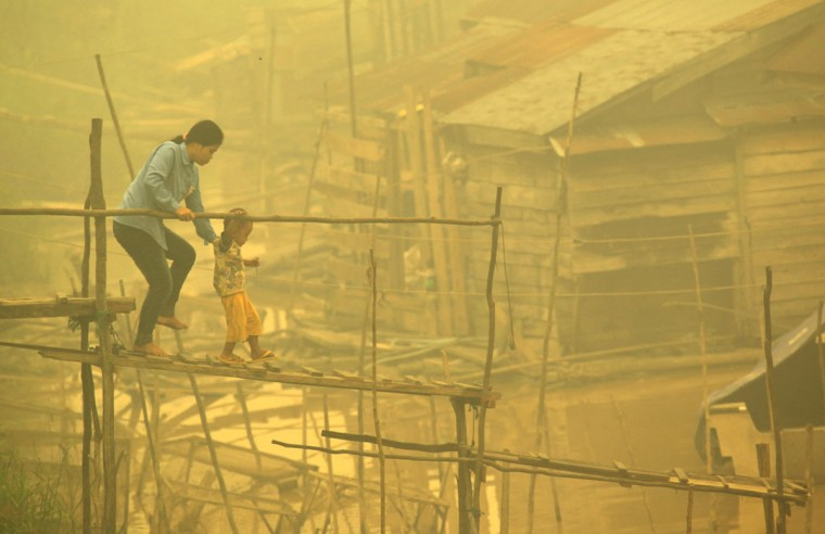 An Indonesian woman and a child walk on a bamboo bridge as thick yellow haze shrouds the city in Palangkaraya on October 22, 2015. Dense haze from Indonesian forest fires has caused some of the worst pollution in southern Thailand for a decade, officials said October 22, cancelling flights in an area popular with tourists. (WISANGGENI/AFP/Getty Images)