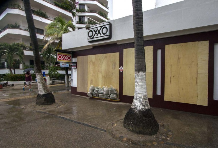 A man passes by a store with their windows blocked off in Puerto Vallarta, Mexico on October 23, 2015. Monster Hurricane Patricia rumbled toward Mexico's Pacific coast on Friday, growing into the strongest storm on record in the Western Hemisphere as the country braced for a potential catastrophe.  || CREDIT: HECTOR GUERRERO - AFP/GETTY IMAGES