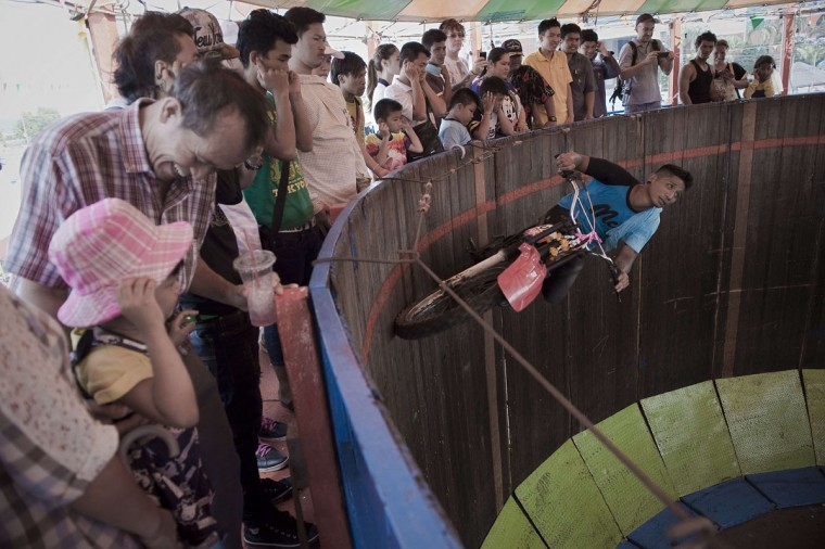A man rides a motorcycle in a cylinder to entertain visitors during the annual buffalo races in Chonburi, southeast of Bangkok on October 26, 2015. (NICOLAS ASFOURI/AFP/Getty Images)