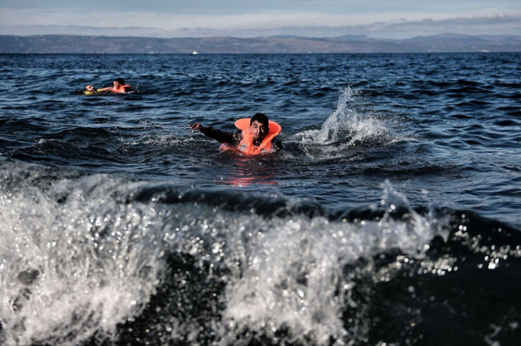 Two men swim toward the Greek island of Lesbos as migrants and asylum seekers cross the Aegean sea from Turkey on Tuesday. More than 700,000 refugees and migrants have reached Europe's Mediterranean shores so far this year, amid the continent's worst migration crisis since World War II, the UN refugee agency said. (ARIS MESSINIS/AFP/Getty Images)