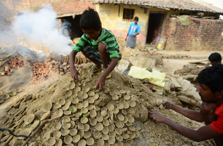 A young Indian potter collects earthen pots drying in the sun to harden them for the upcoming Diwali festival in Allahabad on Tuesday. Diwali marks the victory of good over evil and commemorates the time when Hindu God Lord Rama achieved victory over Ravana and returned to his Kingdom Ayodhya after 14 years of exile. (Sanjay Kanojia/AFP/Getty Images)
