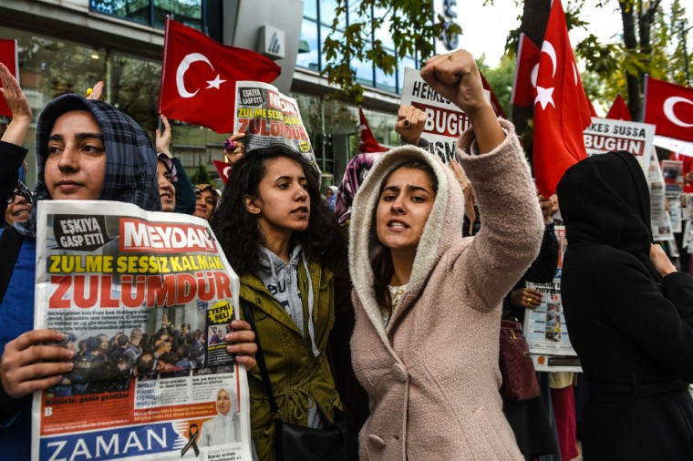 Turkish protesters shout slogans outside the headquarters of Bugun newspaper and Kanalturk television station in Istanbul during a demonstration against the Turkish government's crackdown on media outlets on October 28, 2015. Riot police firing tear gas and water cannon stormed the Istanbul headquarters of a media group linked to President Recep Tayyip Erdogan's bitter rival, on what was described as a dark day for democracy ahead of a pivotal election. The action triggered widespread concern about media freedom in Turkey, with critics accusing the government of trying to silence opponents of Erdogan's Justice and Development Party (AKP) before the November 1 legislative vote. (AFP Photo/Ozan Kose)